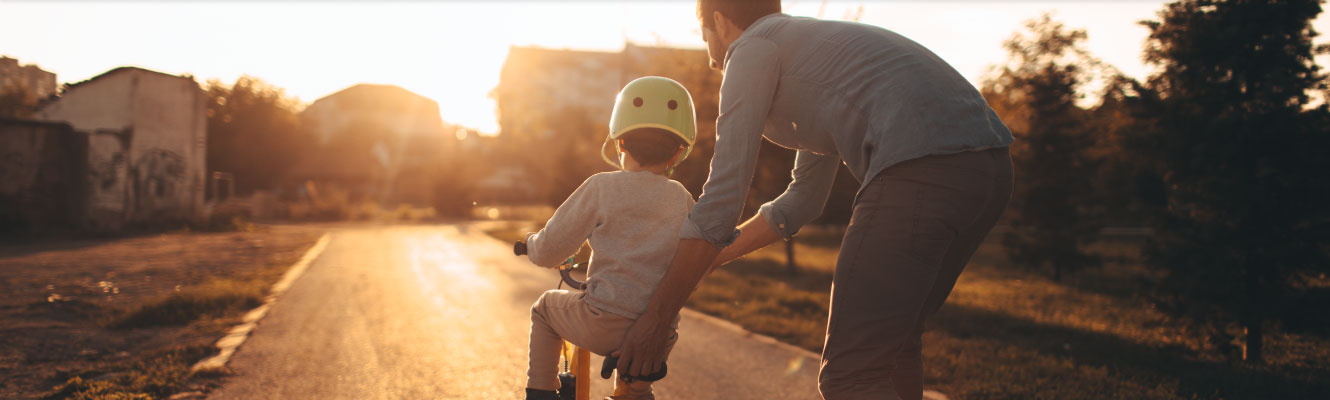 A father helping his son ride a bike for the first time.