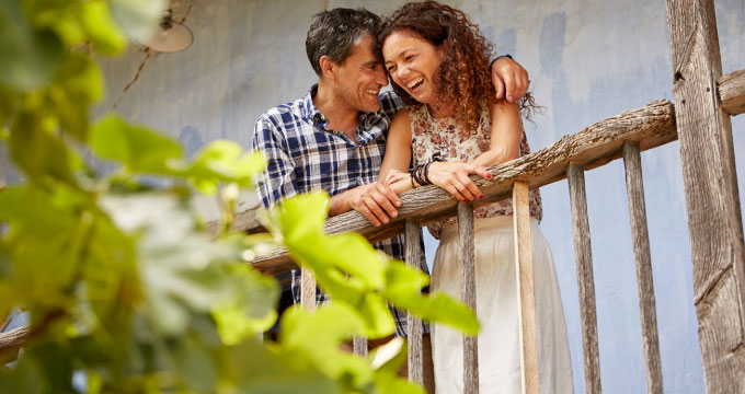 A middle-aged couple laughing and embracing on a house deck.