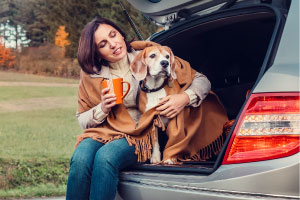 A woman and her dog bundled up in the back of a car.